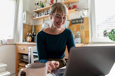 Portrait of happy woman sitting in the kitchen using laptop - p300m2140508 by Kniel Synnatzschke