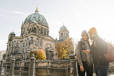 Young couple using smartphone with Berlin Cathedral in background, Berlin, Germany - p300m2154530 by Hernandez and Sorokina