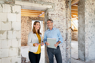 Smiling businesswoman with digital tablet looking away while standing by colleague at construction site - p300m2257146 by Peter Scholl