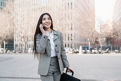 Smiling businesswoman talking on smart phone in city - p300m2265889 by COROIMAGE