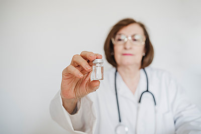 Senior female doctor holding vial in front of white wall - p300m2273971 by Eva Blanco