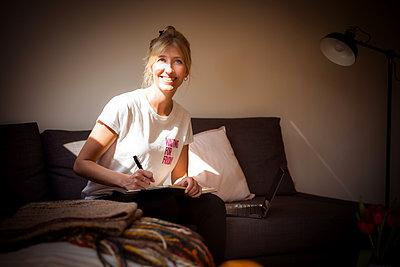 Junge Frau in ihrer Dachwohnung im Sonnenlicht - p741m2176783 von Christof Mattes