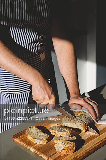 a man cuts bread on a wooden board - p1166m2255971 by Cavan Images