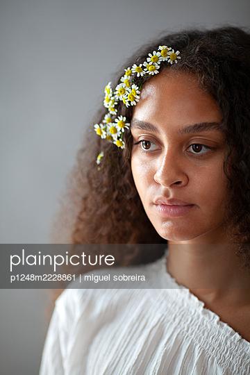 Frau mit Gänseblümchen im Haar - p1248m2228861 von miguel sobreira