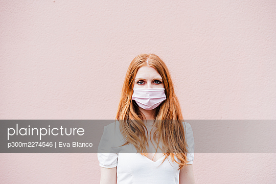 Redhead woman wearing protective face mask while standing in front of pink wall during COVID-19 - p300m2274546 by Eva Blanco