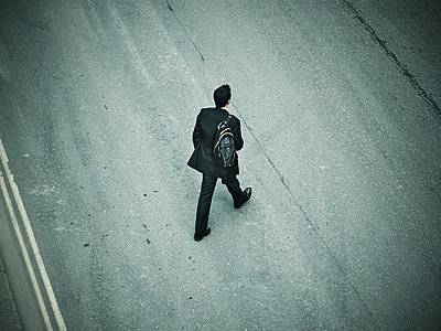 Lone man walking urdan across road - p1072m836372 by Neville Mountford-Hoare