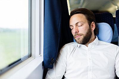 Geschäftsmann schläft im Zug - p1114m1159782 von Carina Wendland