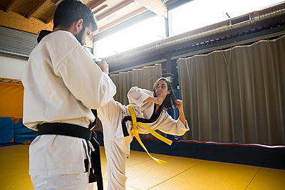 Young man and woman in kimonos practicing hapkido attacks in gym. - p1166m2130118 by Cavan Images