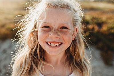 Close up Portrait of young school age girl with freckles smiling - p1166m2165873 by Cavan Images