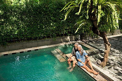 Senior man taking selfie at poolside while his wife is playing the guitar - p300m1535159 by Steve Brookland