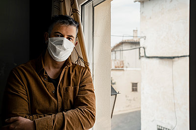 Man wearing protective mask and looking out of the window - p300m2189478 by Rafa Cortés
