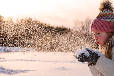 Playful girl in warm clothing blowing snow during winter - p300m2265140 by Ekaterina Yakunina