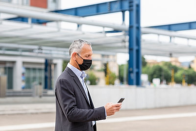 Businessman using smart phone at railroad station during pandemic - p300m2287332 by Emma Innocenti