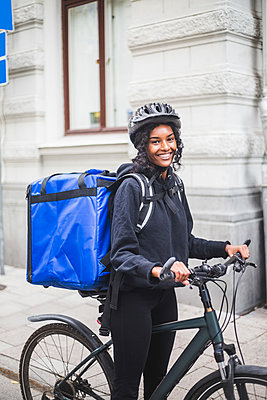 Portrait of smiling delivery woman with bicycle in city - p426m2145423 by Maskot