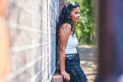 Young woman with long black hair leaning against wall - p429m2138311 by GS Visuals