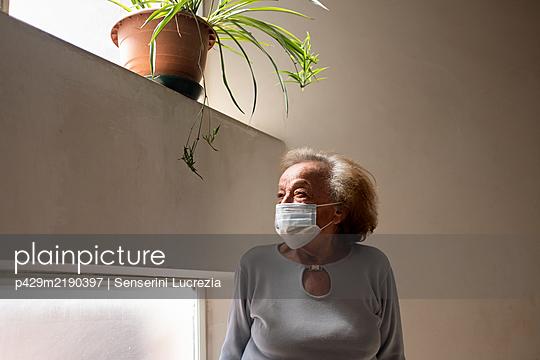 Senior woman wearing face mask standing in her home during Corona virus crisis.  - p429m2190397 by Senserini Lucrezia