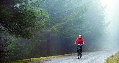 Man mountain biking in rain - p1023m2135908 by Robert Daly