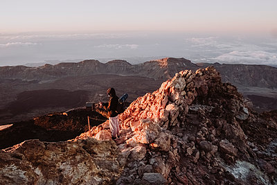 A male hiker watches sunrise from summit of El Teide - p1166m2124335 by Cavan Images