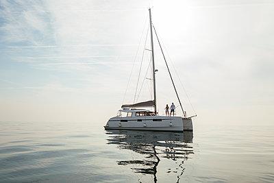 Couple setting off for a sailing trip on a catamaran - p300m2012491 von Bonninstudio