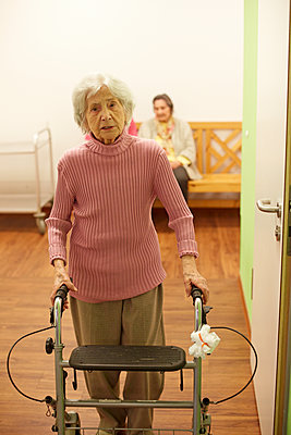Age demented senior woman with wheeled walker in a nursing home - p300m2219201 by Heinz Linke