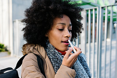 Afro young woman applying lipstick while standing on street - p300m2256861 by Xavier Lorenzo