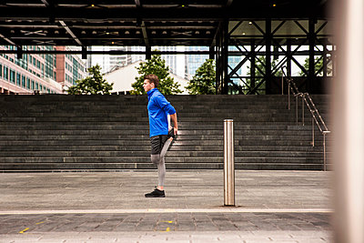 Young runner stretching on pavement, London, UK - p429m2075350 by Tom Dunkley