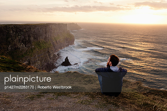 Mid adult man sitting on The Cliffs of Moher, The Burren, County Clare, Ireland - p1427m2283170 by Roberto Westbrook