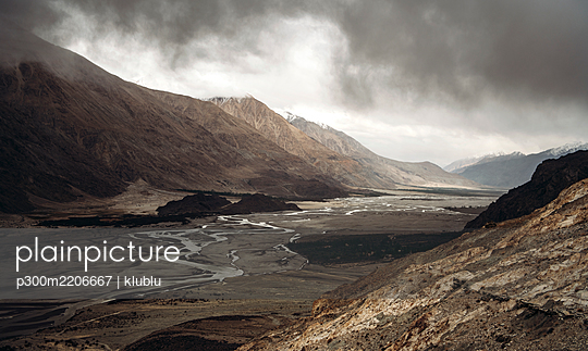 India, Ladakh, Clouds over narrow stream flowing across valley in Himalayas - p300m2206667 by klublu