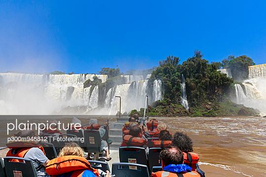 South America, Argentina, Parana, Iguazu National Park, Tourists in a boat at Iguazu Falls - p300m948812 by Fotofeeling