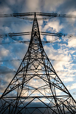 Electricity pylon against cloudy sky - p1047m967971 by Sally Mundy