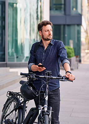 Bicycle courier using smartphone - p1124m2052990 by Willing-Holtz