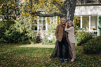 Senior couple in garden of their home in autumn - p300m2156231 by Gustafsson