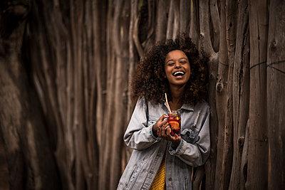 Portrait of laughing woman drinking fresh ice tea drink - p300m2171219 by Malte Jäger