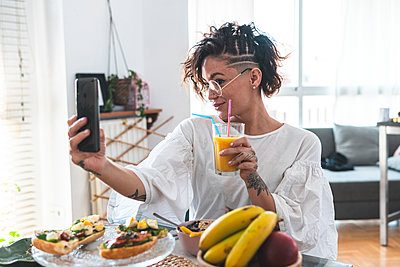 Portrait of young woman taking smart phone selfie while eating breakfast - p300m2242711 by Josu Acosta