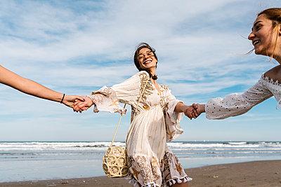 Happy woman holding hands of friends at beach - p300m2275007 by Ezequiel Giménez