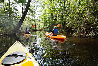 Caucasian men kayaking in jungle - p555m1464316 by Roberto Westbrook
