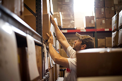 Worker reaching up for cardboard box stored in warehouse - p924m825949f by heshphoto