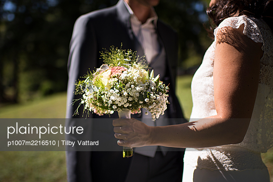 Bride and groom  with bridal bouquet - p1007m2216510 by Tilby Vattard