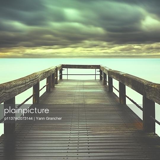 Steg unter düsteren Wolken - p1137m2073144 von Yann Grancher