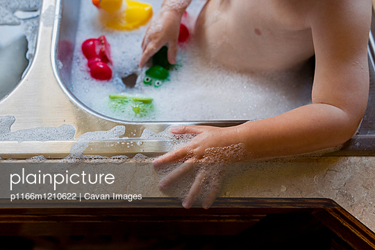 Midsection of shirtless boy playing with water in sink - p1166m1210622 by Cavan Images
