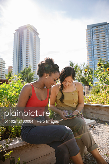 Young women friends using smart phones in sunny, urban community garden - p1192m2130084 by Hero Images