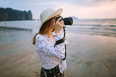 Young woman photographing on beach in Krabi, Thailand - p1427m2110269 by Oleksii Karamanov