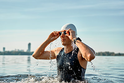 Young athlete in rubber cap holds on swimming goggles - p1630m2196896 by Sergey Mironov