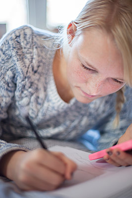 Teenage girl writing on bed - p312m1107658f by Christina Strehlow