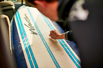 A Surfer Waxing His Surfboard In The Car - p343m1443989 by Josh Campbell