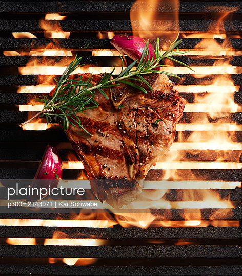 Directly above shot of fresh steak grilling and onion with herb on barbecue - p300m2143971 by Kai Schwabe
