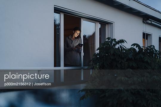 Woman standing in balcony door, using digital tablet - p300m2156312 by Joseffson