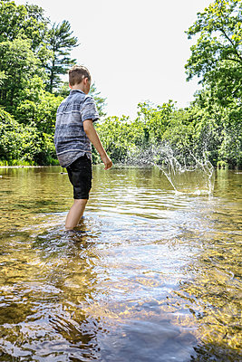 Boy throwing stone into river - p1019m1462180 by Stephen Carroll