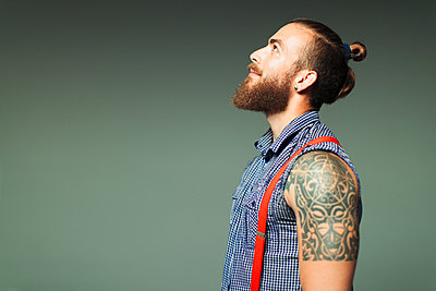 Curious hipster man with beard and shoulder tattoo looking up - p1023m2033463 by Paul Bradbury