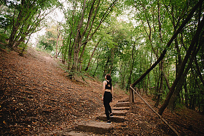 Rear view of female jogger standing on steps in park looking up - p1166m2095783 by Cavan Images